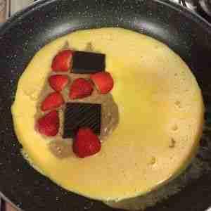 Foto preparando la crepe de huevo con mantequilla de cacahuete, chocolate y fresas