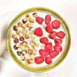 Yogur natural con plátano machacado, frambuesas y avellanas