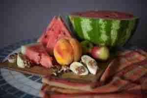 Foto con opciones de meriendas: sandia, melocotón, plátano y nueces